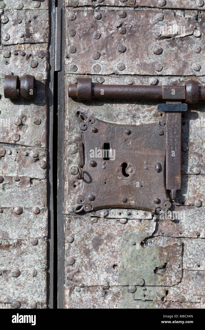 Medieval security - An old lock and a heavy bolt on a fortrass door in Seville in Andalusia, Spain. - Stock Image