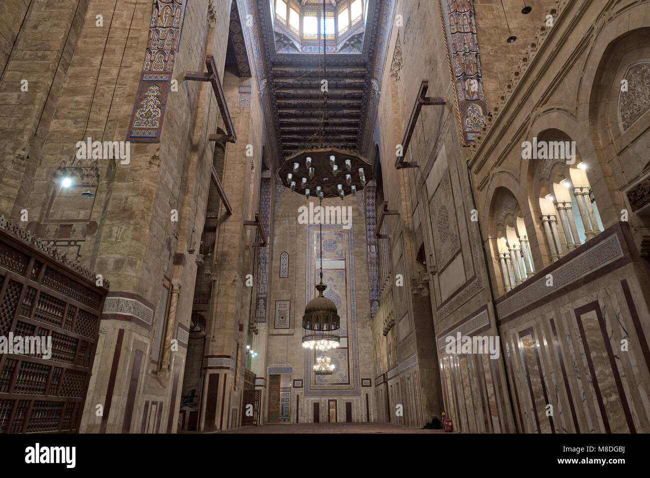 Interior of al Refai mosque with old decorated bricks stone wall, colored marble decorations, wooden ornate ceiling, - Stock Image