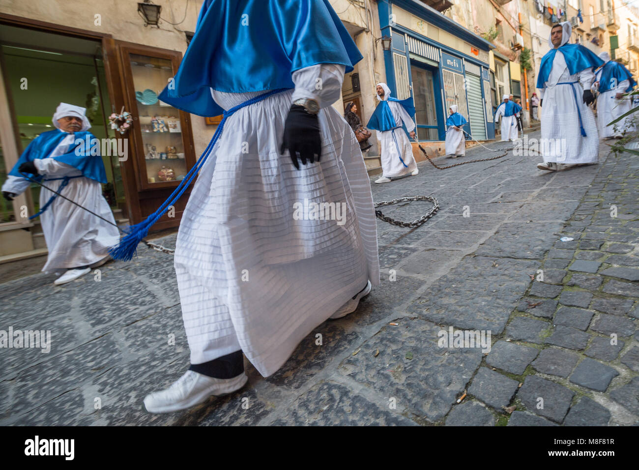 PROCIDA, ITALY - MARCH 25, 2016 - Some Turchini Brothers walk on the cobbled paving dragging chains during the Procida's - Stock Image