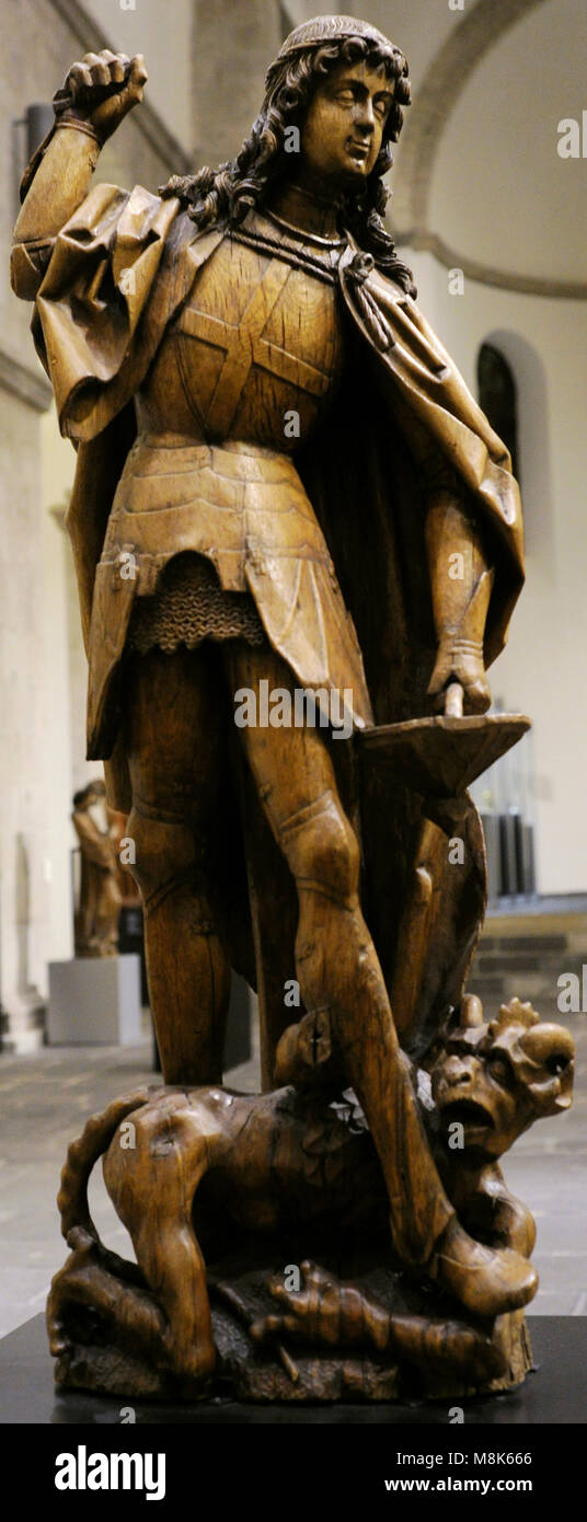 Saint Michael. One of the archangels. Sculpture depicting Saint Michael fighting against Satan. Meuse region, Germany, - Stock Image