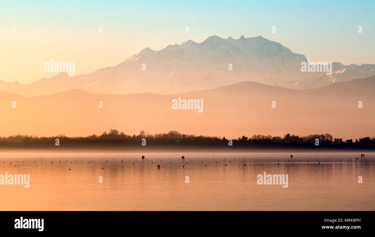 Pastel colors at sunset and Monte Rosa seen from lake of Varese in winter afternoon - Stock Image