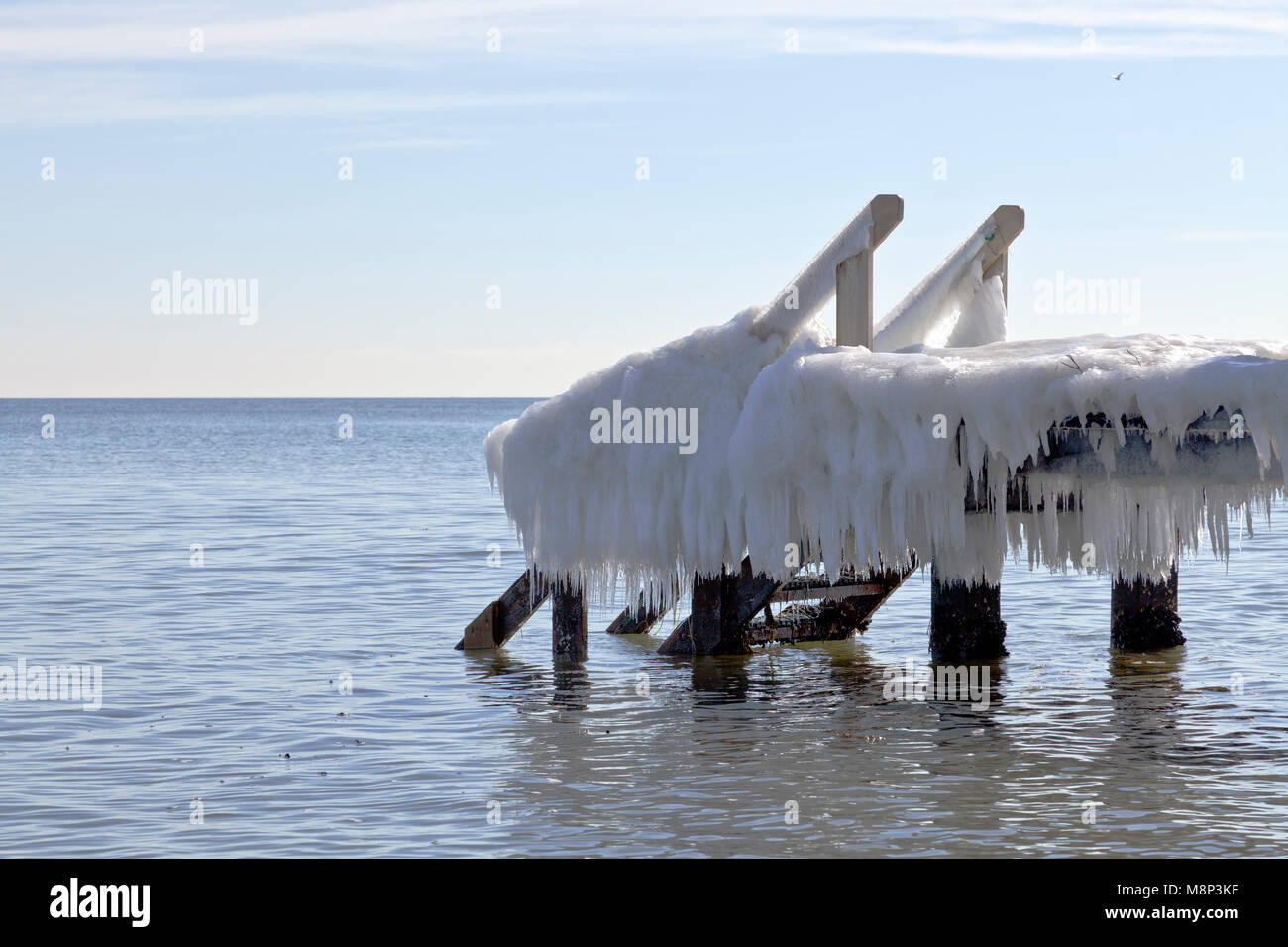 Ice formations and icicles on a bathing jetty at spring on a sunny day in the Sound / Oresund close to Copenhagen - Stock Image