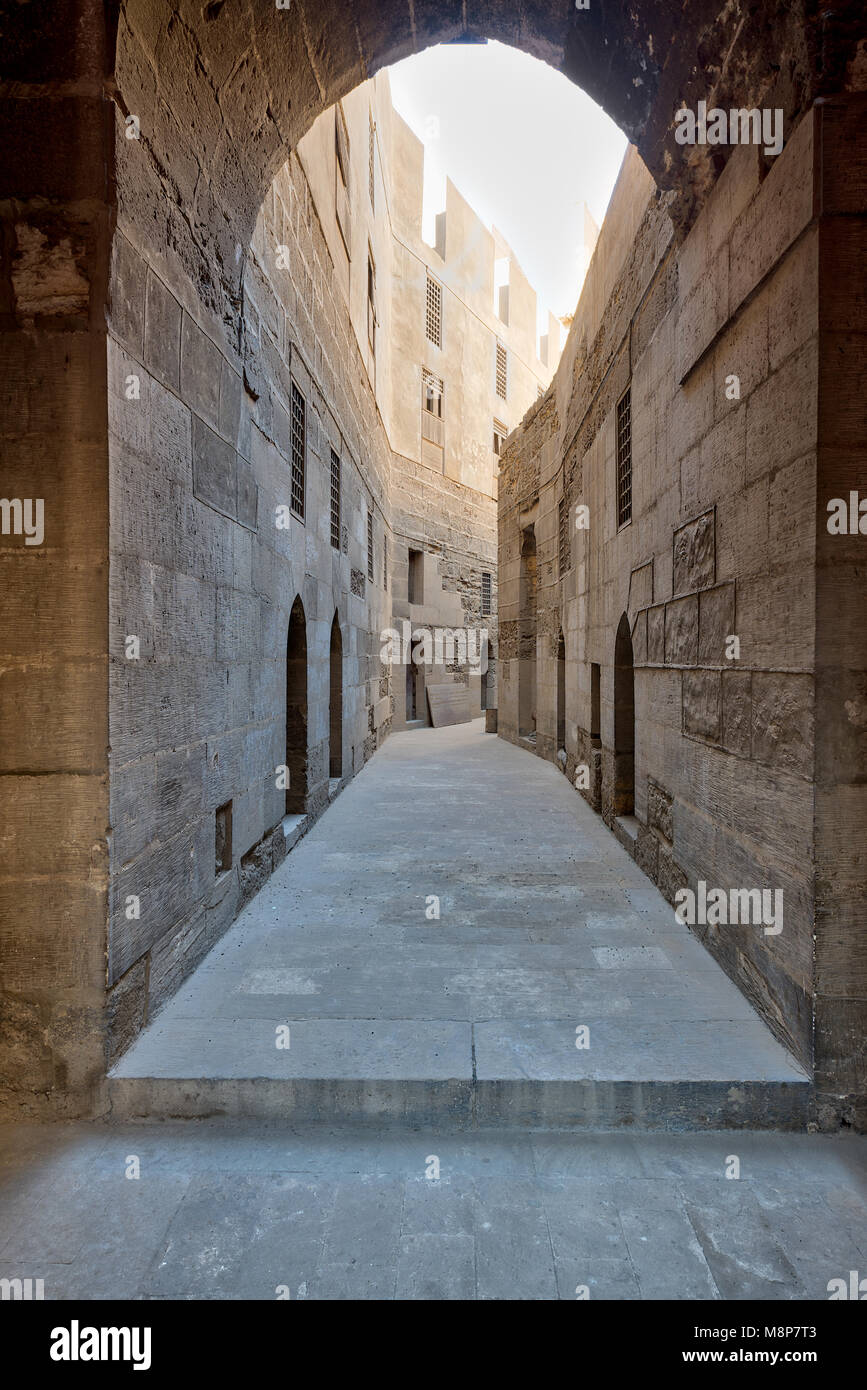 Narrow passage with old grunge stone walls leading to Sultan Hasan Mosque, Cairo, Egypt - Stock Image