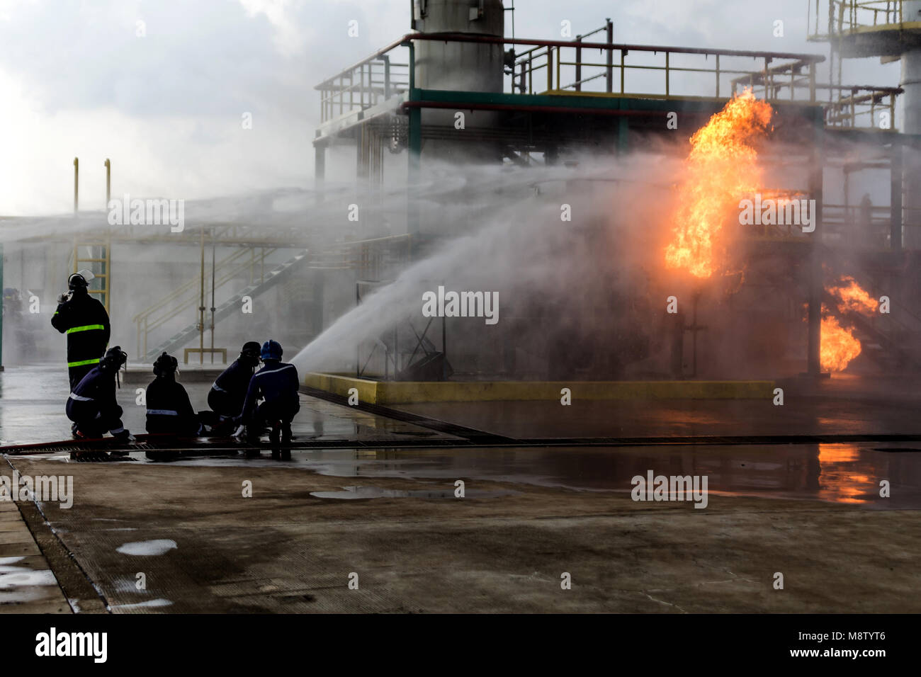 Firemen using water from hose for fire fighting at firefight training of insurance group. Firefighter wearing a - Stock Image