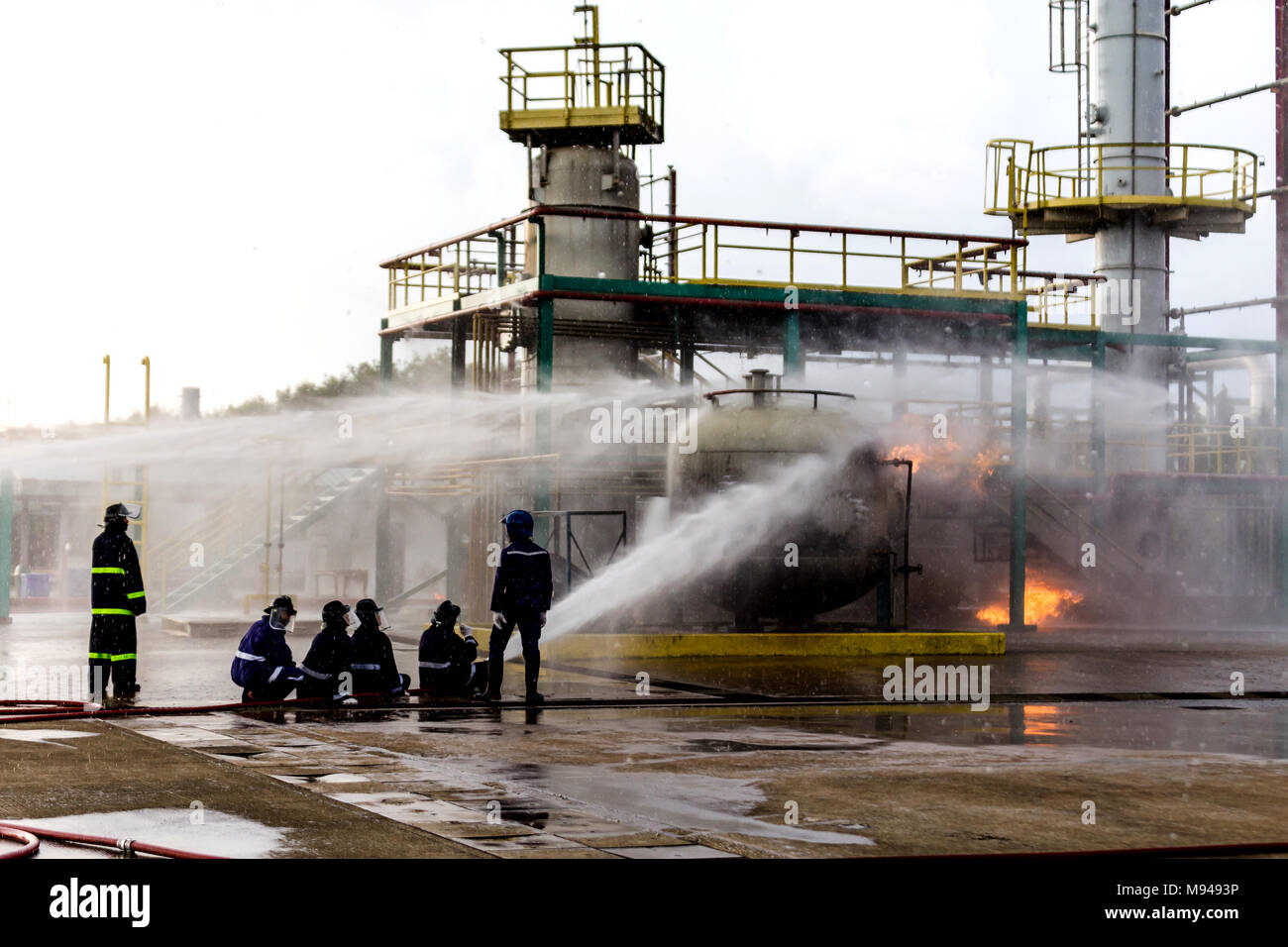 Firemen using water from hose for fire fighting at firefight training of insurance group. Firefighter wearing a fire suit for safety under the danger  - Stock Image