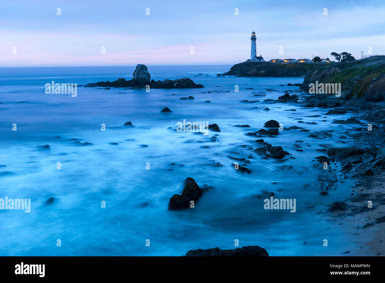Picturesque historic Pigeon Point Lighthouse, Pescadero, breaking waves on the Pacific Coast of California at dusk, United States of America, USA. Stock Photo