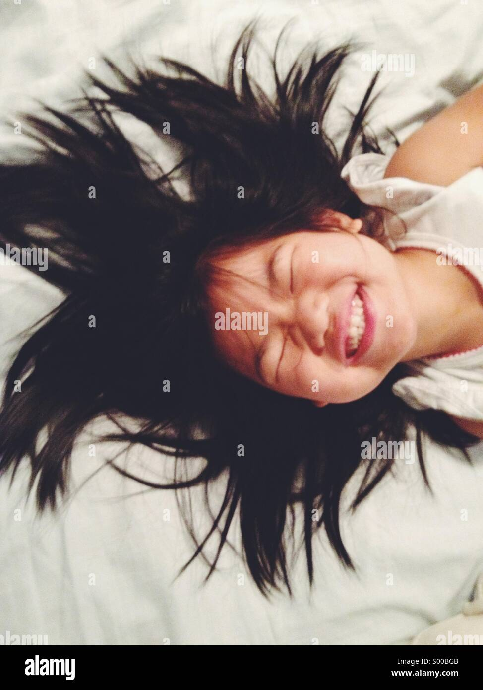 Young girl laying on bed smiling Stock Foto
