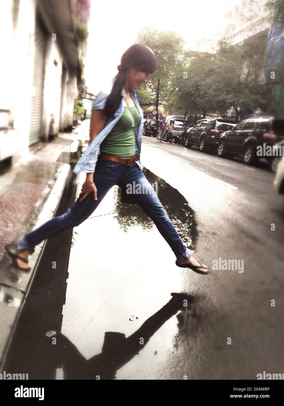 Asian girl stepping over puddle in Saigon hcmc Vietnam Stock Foto