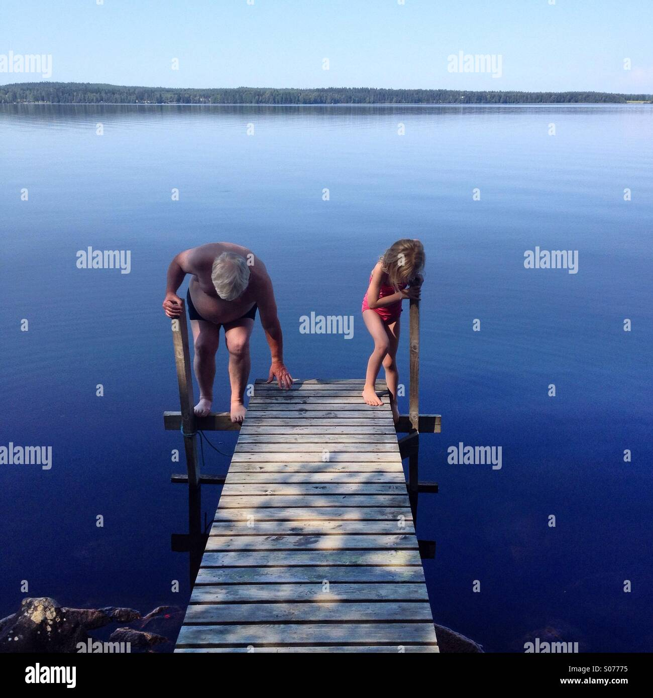 Grandfather and granddaughter go swimming in a Nordic lake together Stock Foto