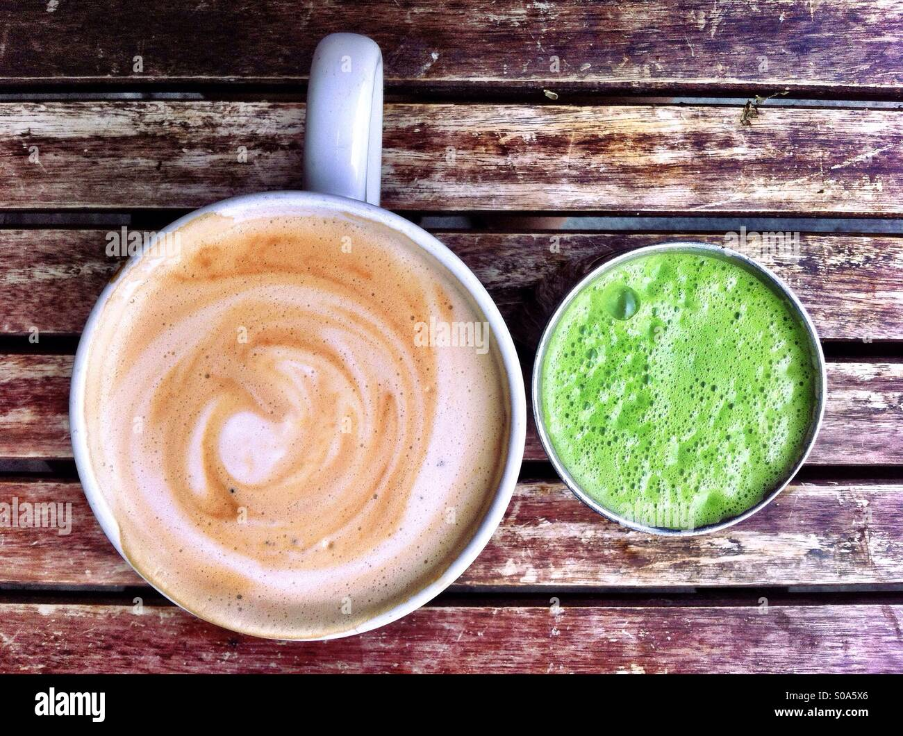 Cup of cappuccino and glass of green juice on rustic wooden table Stock Foto