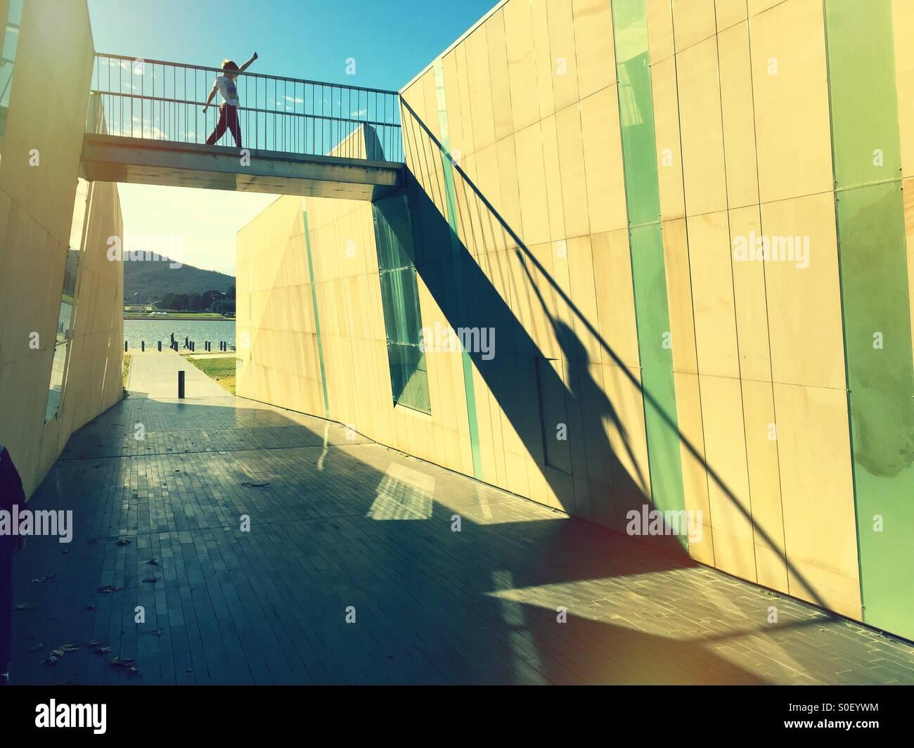 A boy striding across a bridge over an underpass Stock Foto