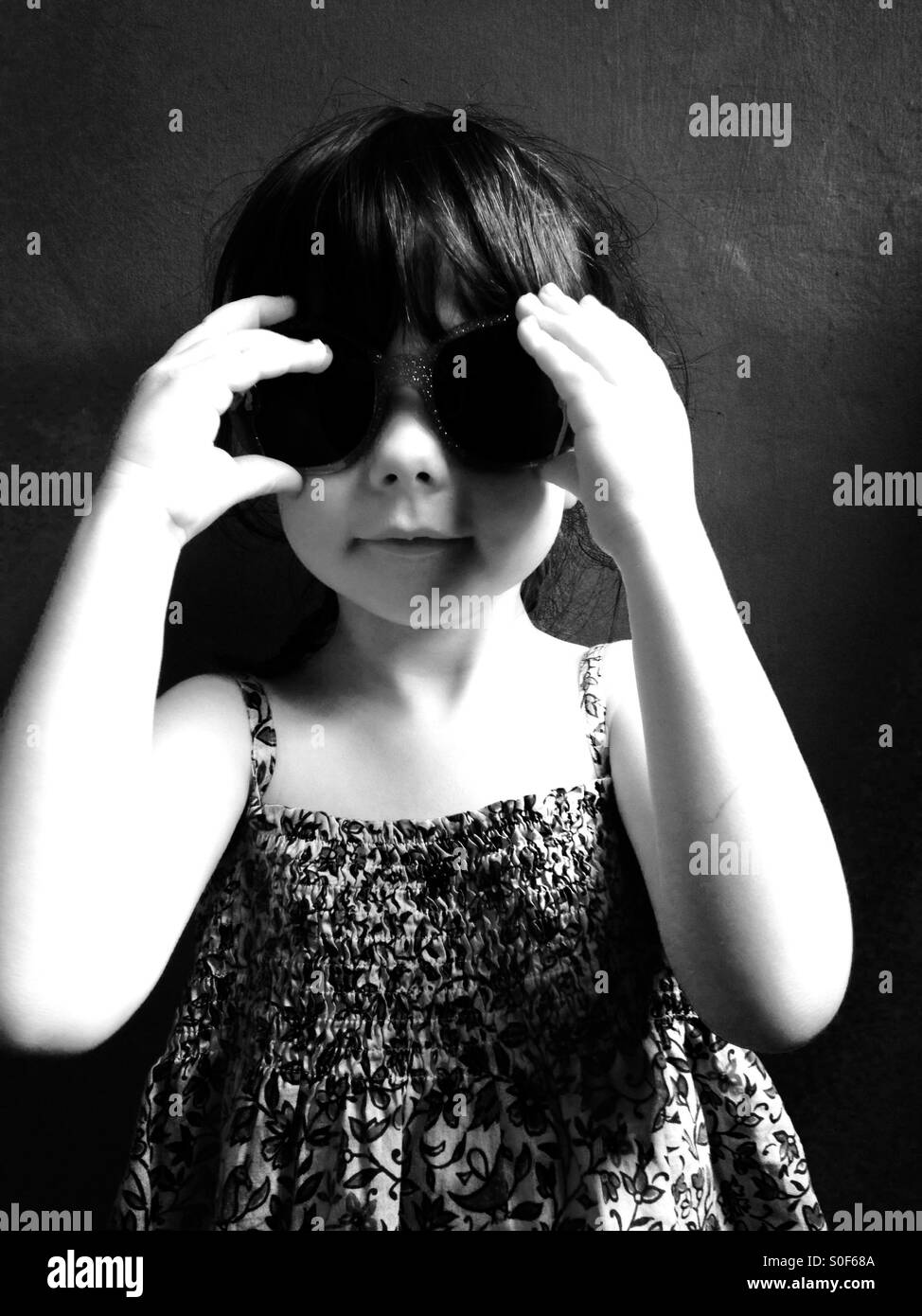 3-year old girl wearing sunglasses and summer dress. Stock Foto