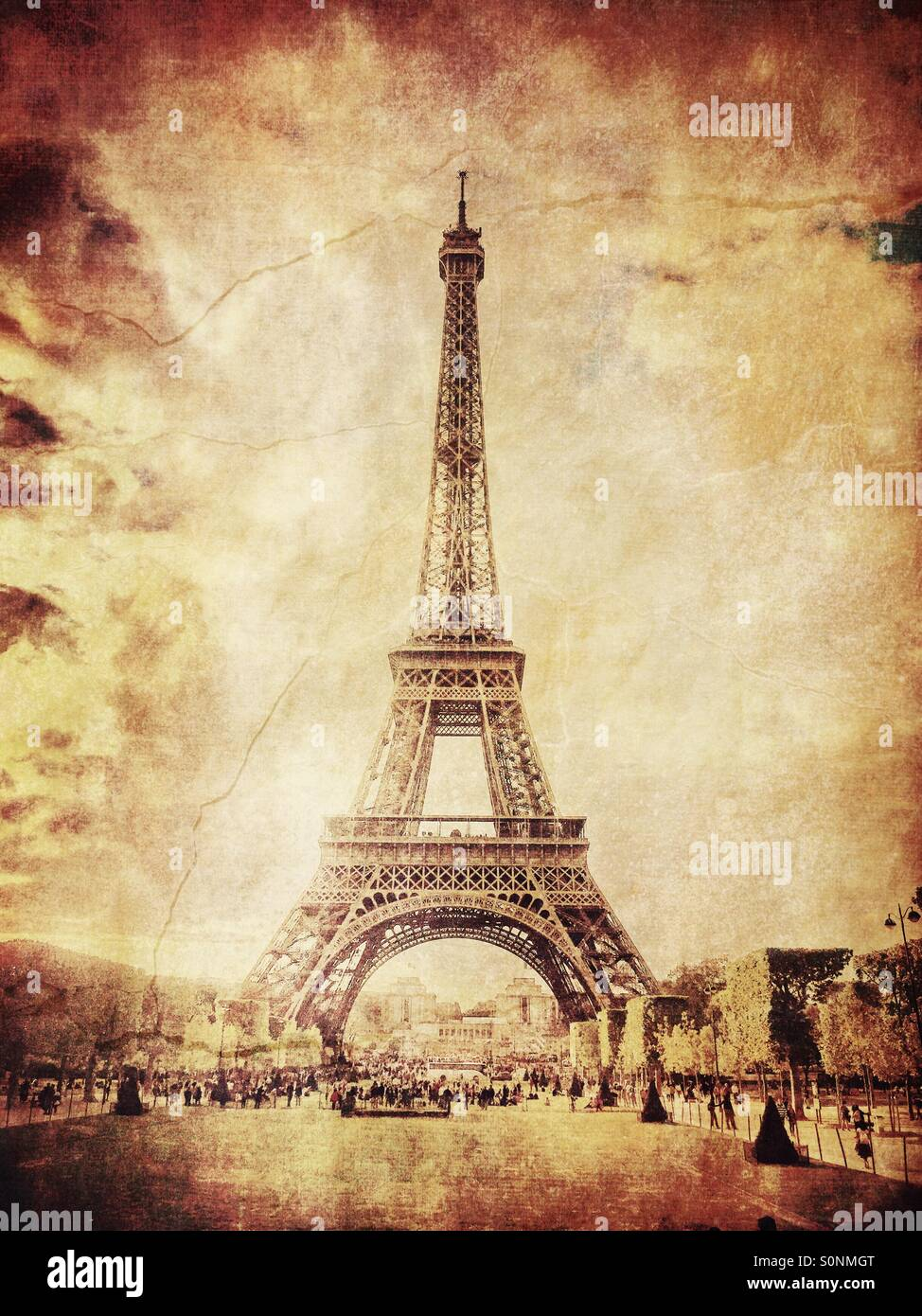 View of Eiffel Tower from Champs de Mars in Paris, France. Aged sepia tones and vintage paper texture overlay. Stock Photo