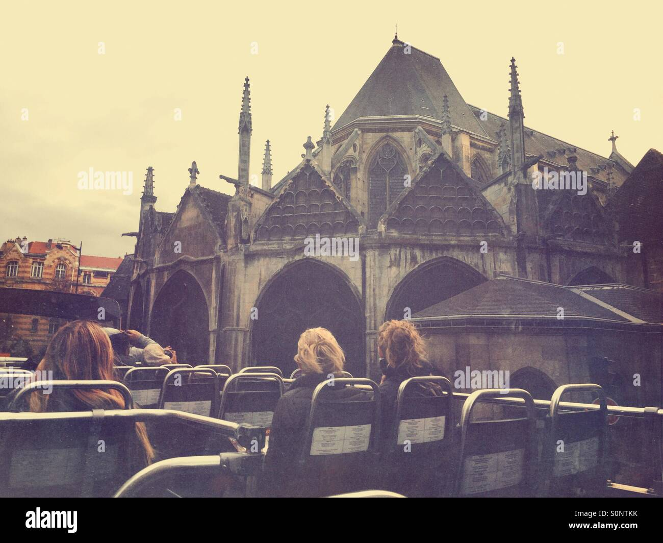 Tourists view an old building on the 5th arrondissement from roof of open air sightseeing bus in Paris, France. Stock Photo