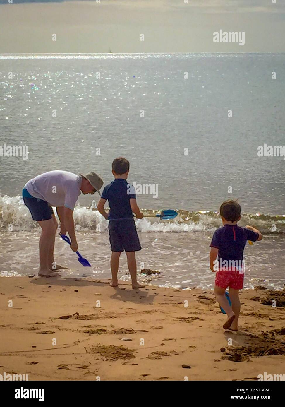 a-family-playing-on-the-beach-at-dawlish-warren-in-devon-uk-S13B5P.jpg
