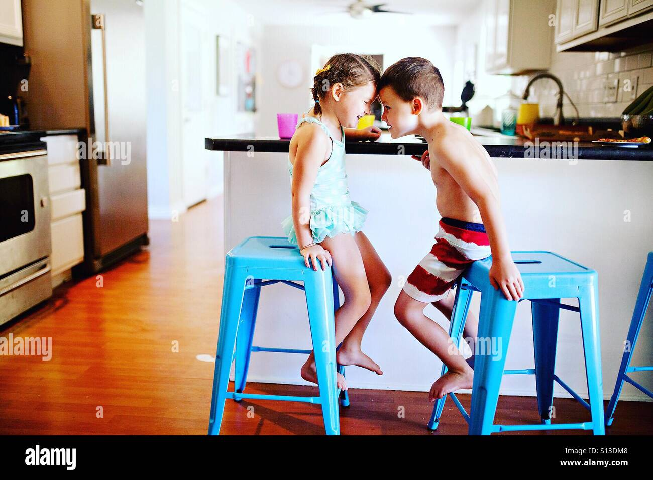 Two children in swim suits being silly at meal time at home in modern kitchen Stock Foto