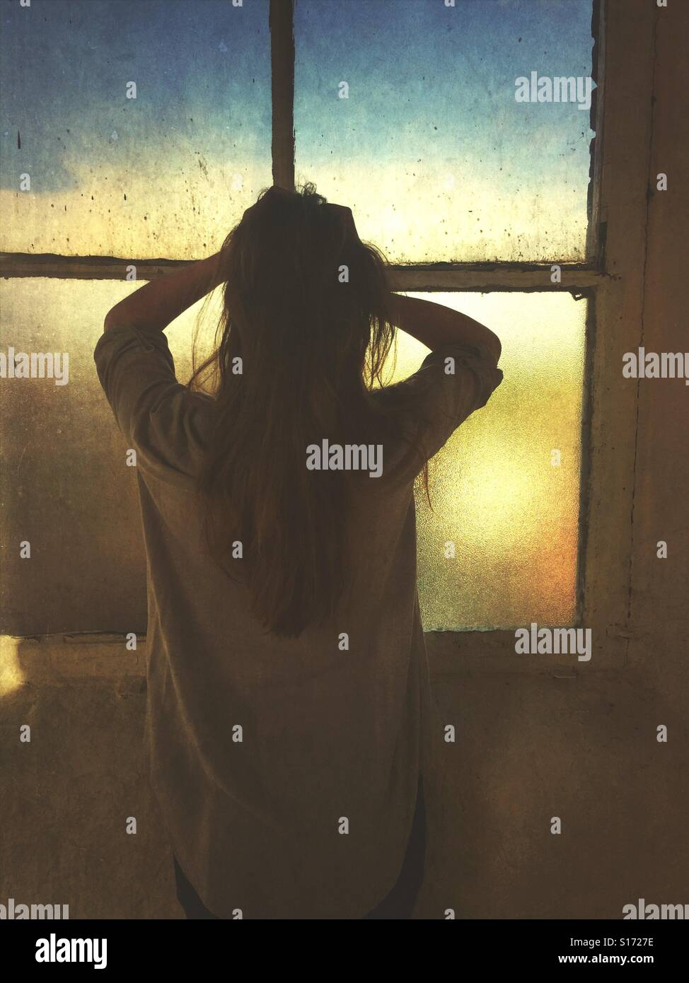 Rear view of a stressed woman head in hands by the window Stock Foto