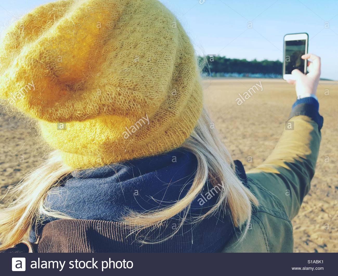Pretty blonde with phone on beach. Stock Foto