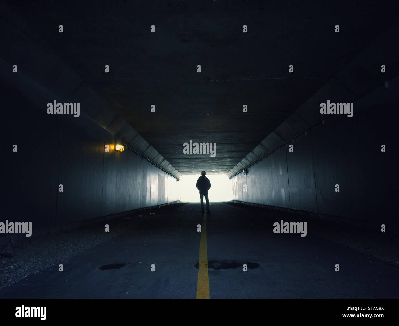 Man standing in the end of a dark tunnel Stock Foto