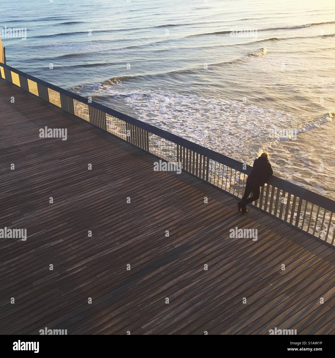 Man leaning over Hastings pier looking at the sea Stock Foto