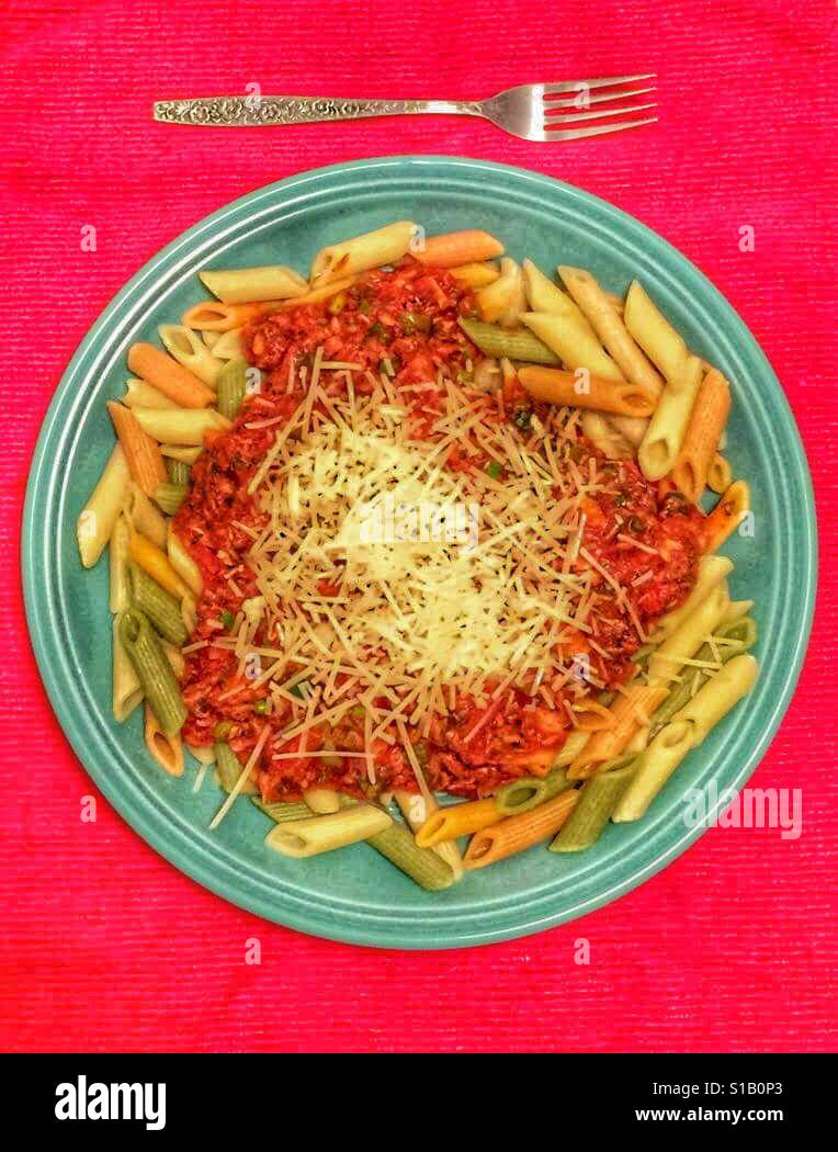 Penne alla Putanesca. A turquoise colored dinner plate sits on a bright red tablecloth, containing colorful penne Stock Foto
