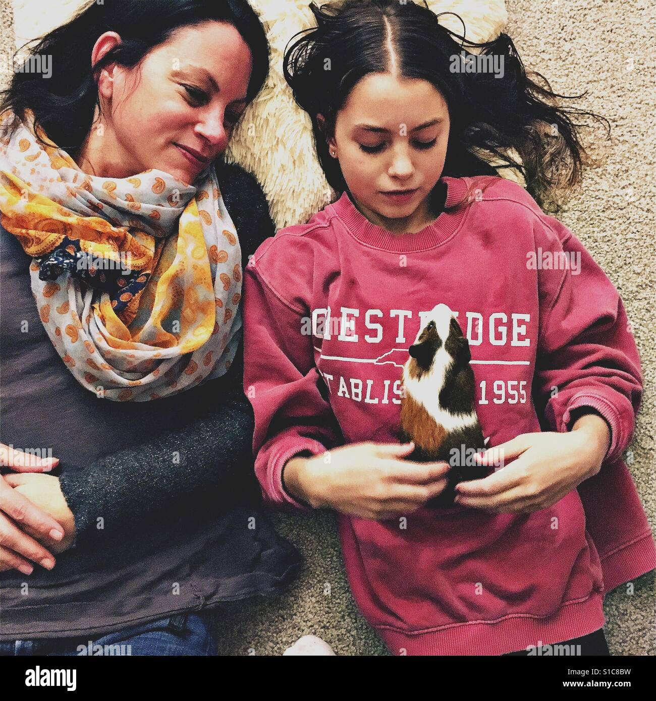 Mother and daughter with guinea pig Stock Foto