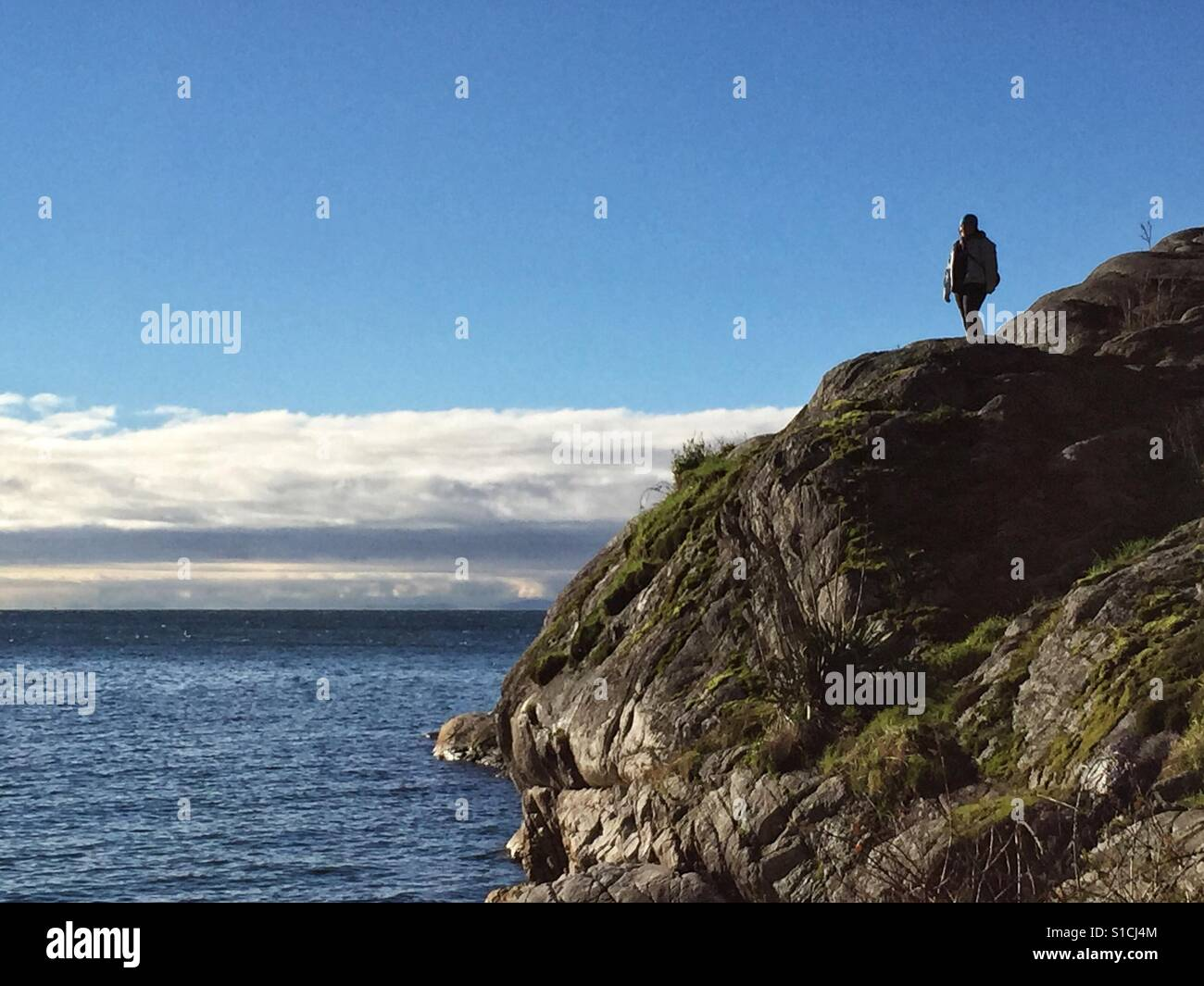 Solitary person at the edge on a cliff next to the sea, looking at the marine landscape. Stock Foto
