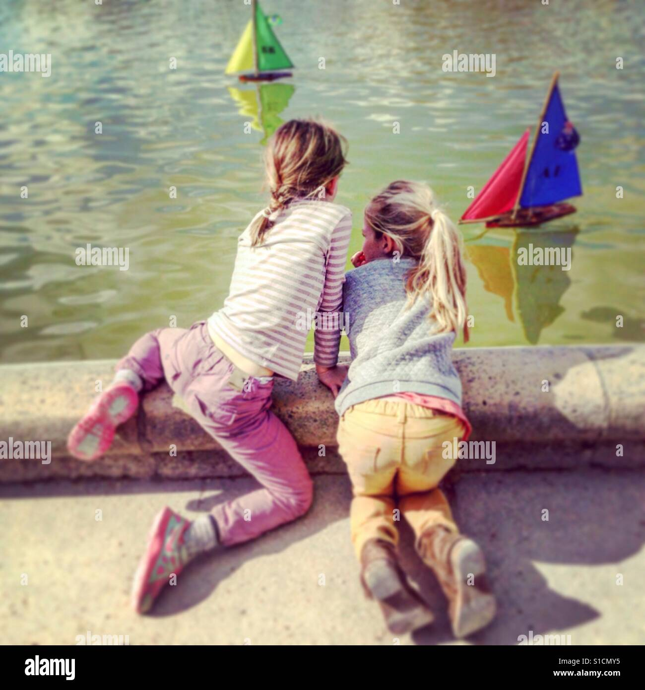 Girlfriends watch the toy boats at Luxembourg Park Paris, France. Stock Foto