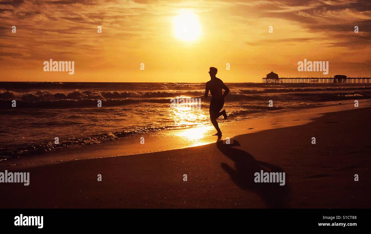 Young man running on the beach at sunset in California. Stock Foto