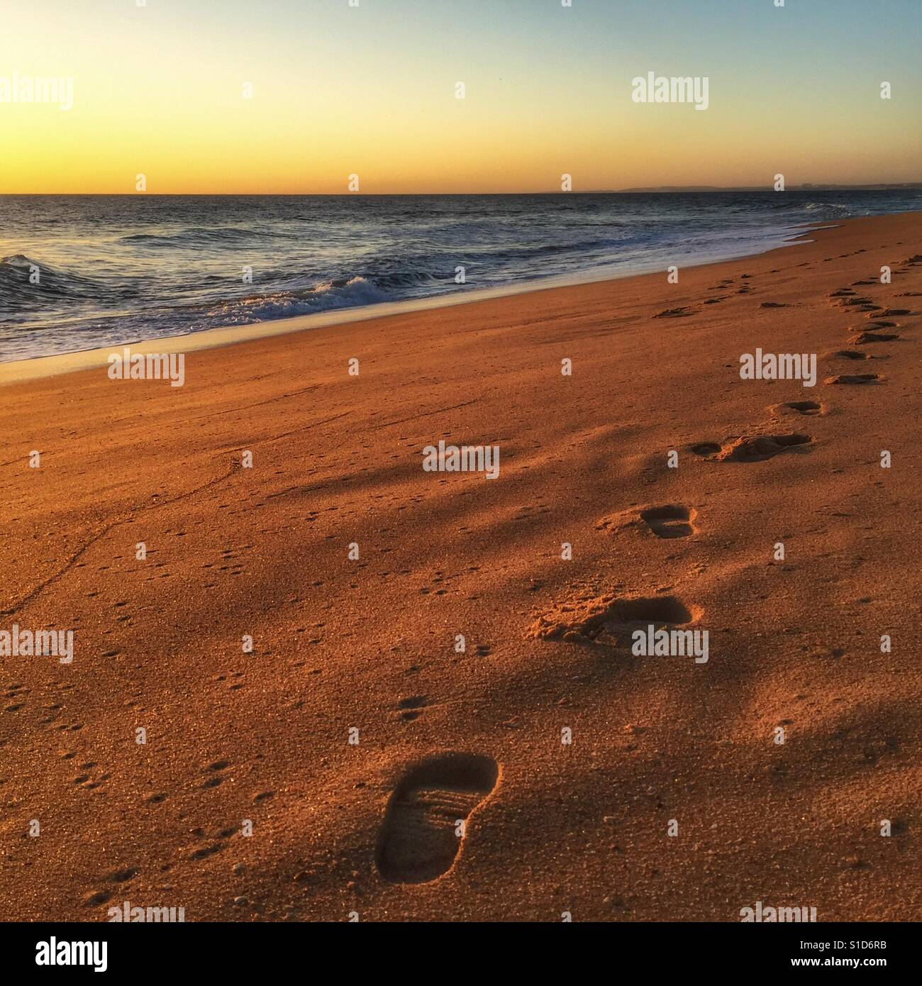 Sunset on a beach in Portugal with foot prints in the sand leading of in to the horizon. Stock Foto
