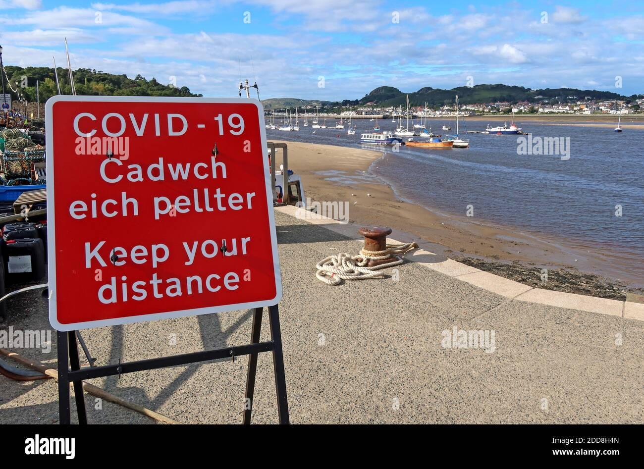 Dieses Stockfoto: Conwy Quay, Strand, Covid-19, halten Sie Ihre Entfernung, Schilder, am Hafen, North Wales, Großbritannien, LL32 - 2DD8H4