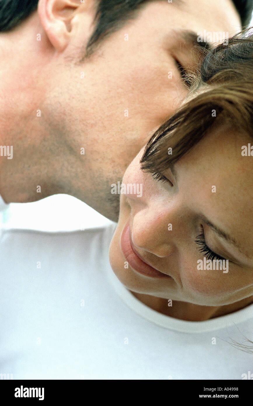 Porträt eines jungen Mannes küssen eine Frau Ohr hautnah Stockbild
