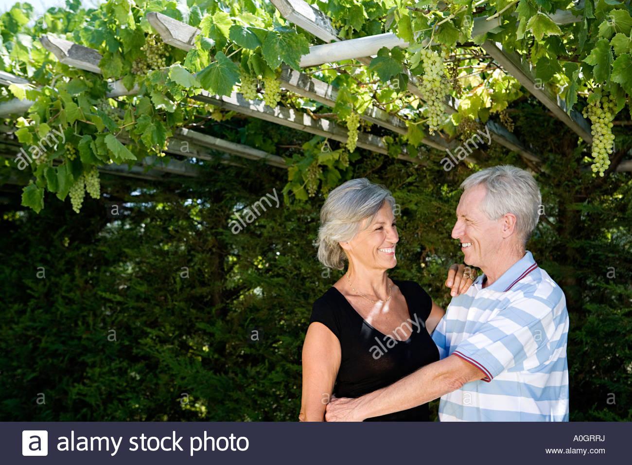 Paar unter Weinreben Stockbild