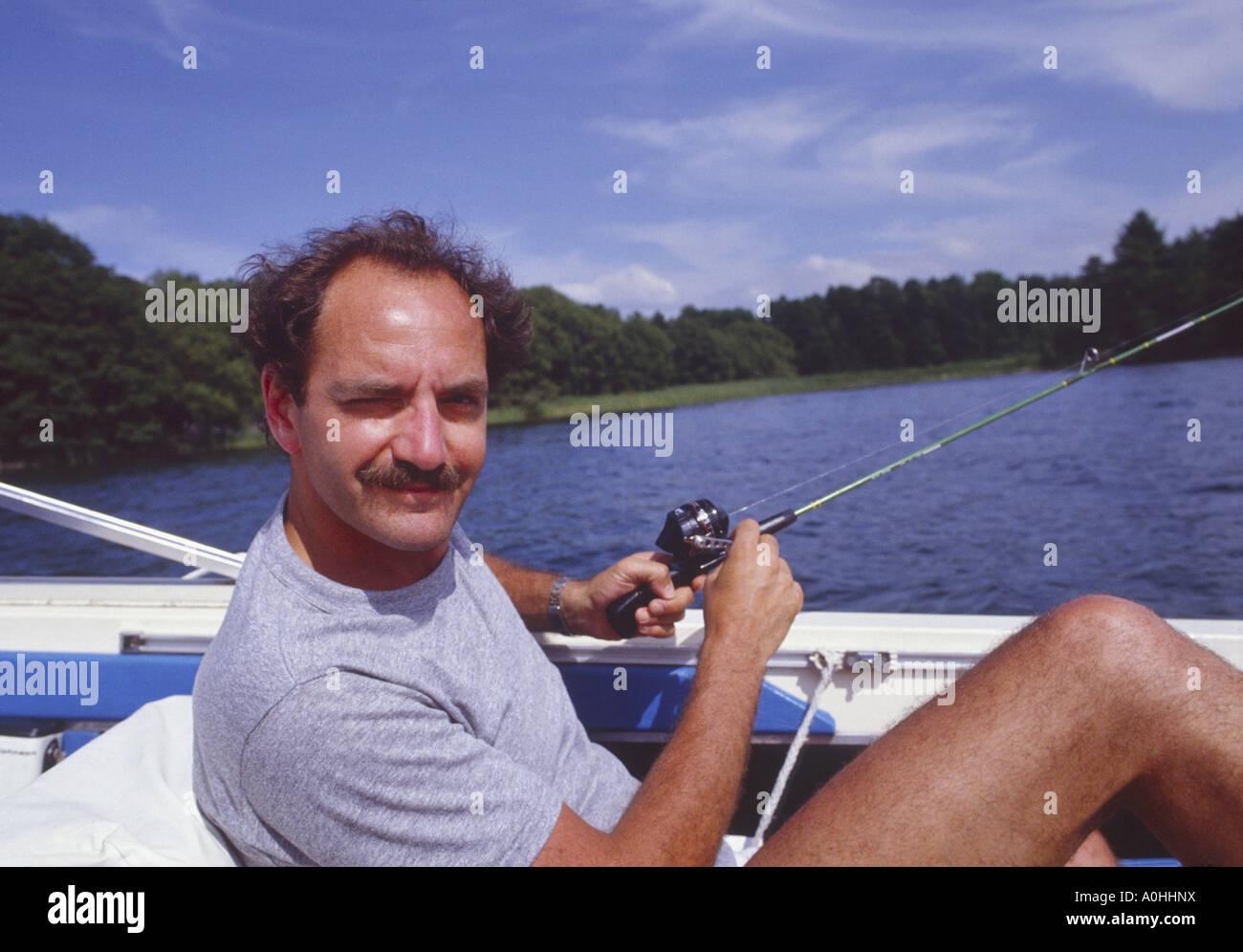 Mann im Boot mit preiswerten Rute und Rolle Angeln Stockbild