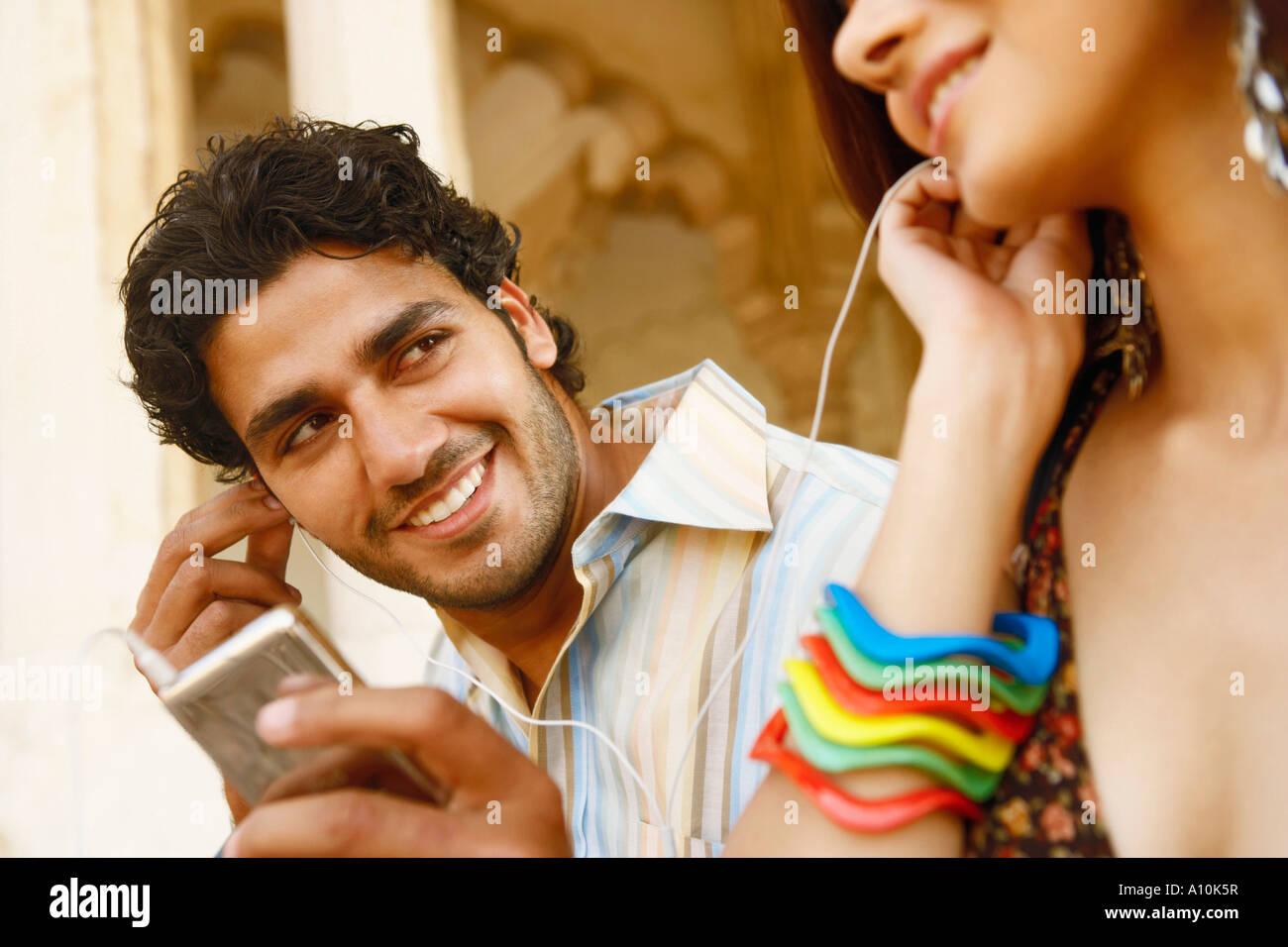 Nahaufnahme eines jungen Paares, das Anhören von Musik über Kopfhörer, Agra Fort, Agra, Uttar Pradesh, Stockbild
