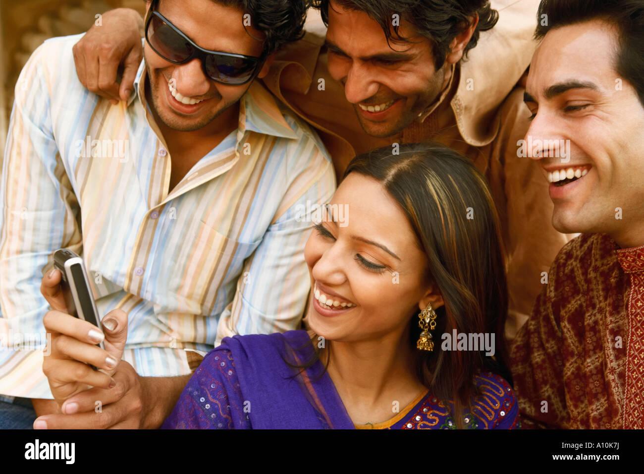 Nahaufnahme von drei junge Männer und eine junge Frau mit Blick auf ein Mobiltelefon und lächelnd, Agra, Stockbild