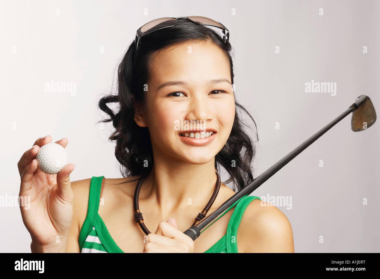Porträt einer jungen Frau hält ein Golfclub und ein Golfball Stockbild