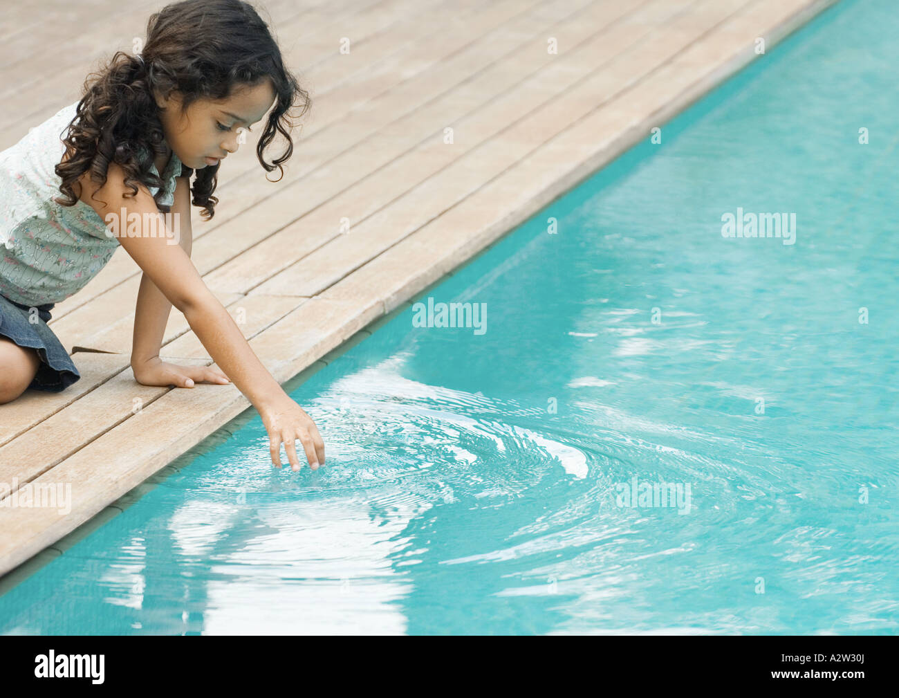 Kleines Mädchen sitzt vom Rand des Schwimmbads berühren der Oberfläche des Wassers Stockbild