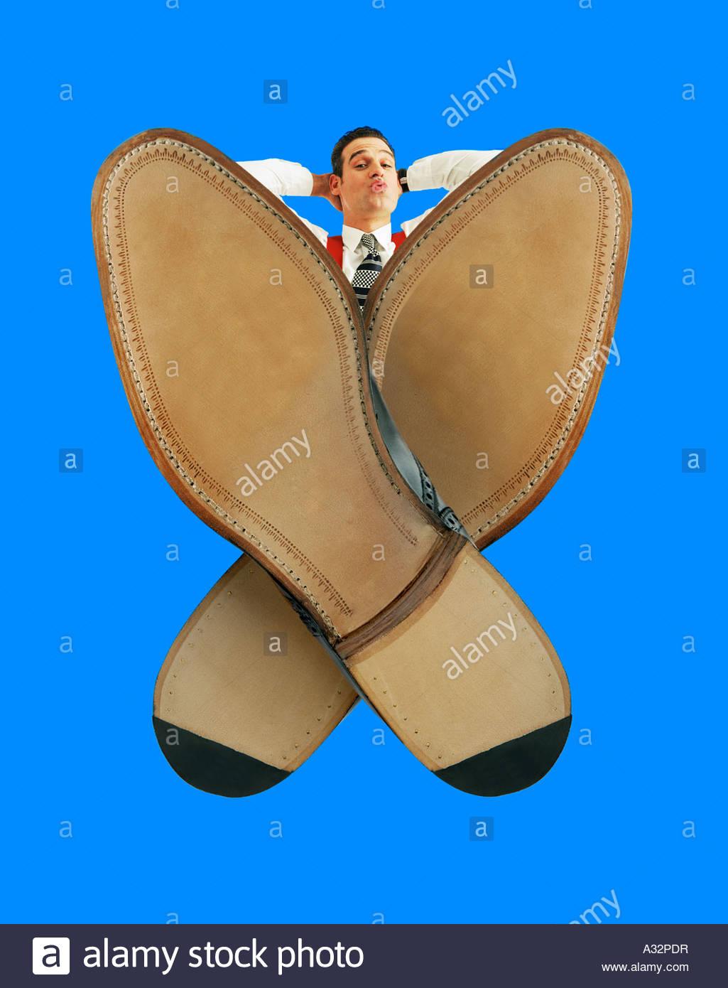 Entspannt, blickte Man mit den Füßen auf dem Schreibtisch, überquerten. Extreme Weitwinkel-Wirkung. Stockfoto
