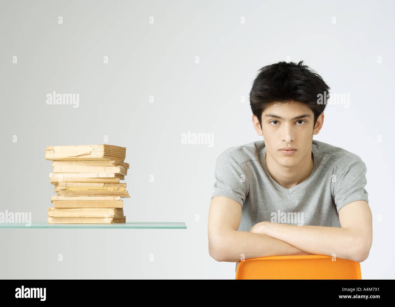 Junger Mann sitzt neben Stapel Bücher, Porträt Stockbild