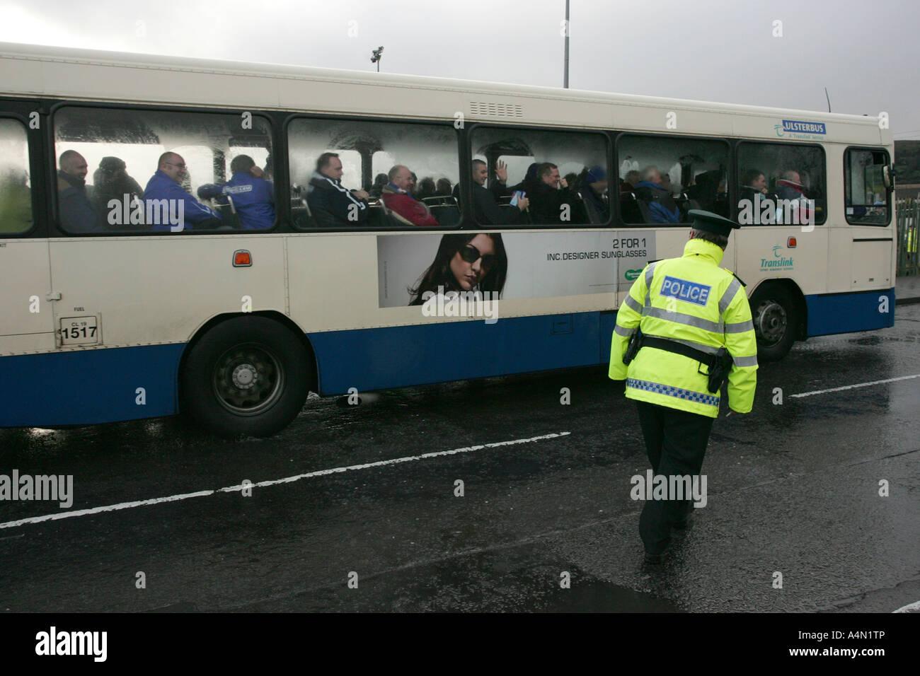PSNI Polizist in Hallo Vis Jacke begleitet Ulster Bus voller Linfield Anhänger durch katholische republikanischen Stockbild