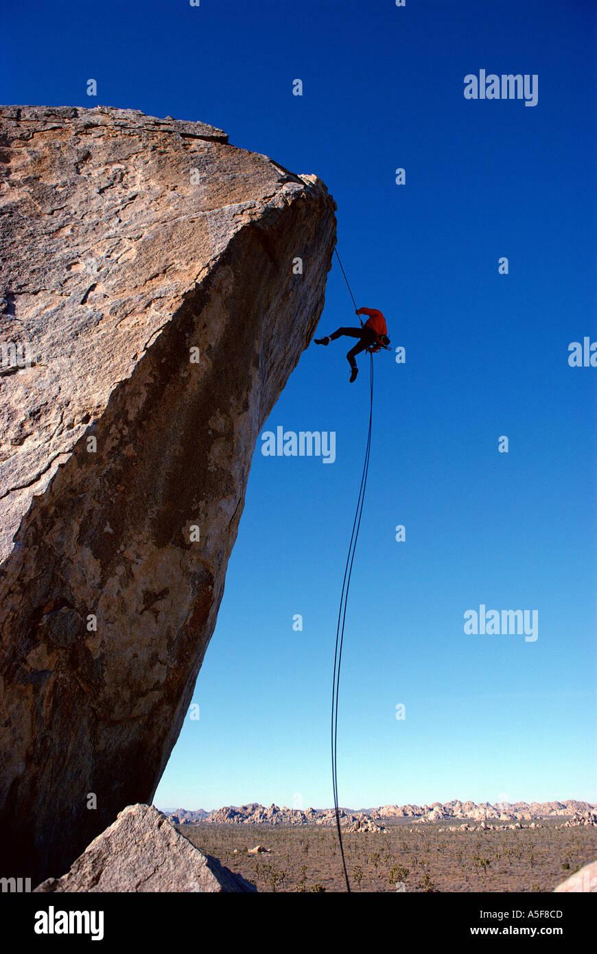 Mann Abseilen aus großen Felsbrocken beim Klettern in Joshua Tree Kalifornien Stockbild