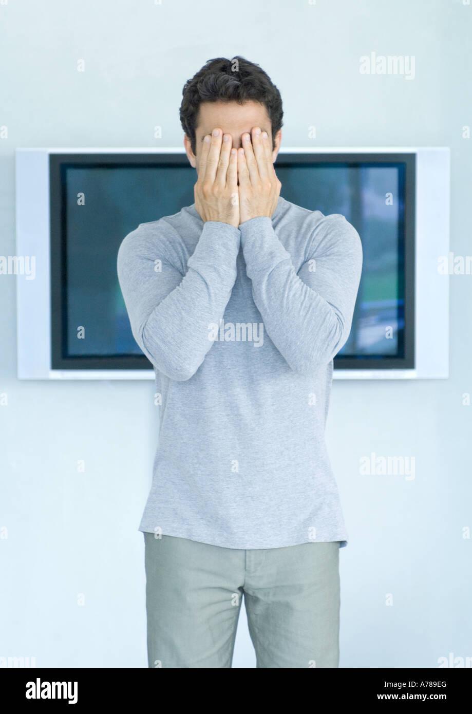 Mann stand vor Breitbild-TV, Hände, Gesicht Stockbild