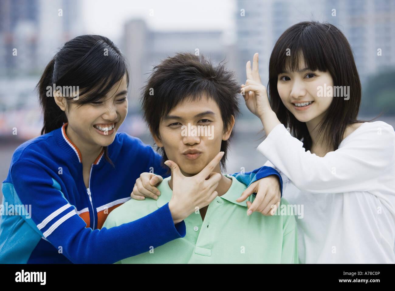 Drei junge Erwachsene Freunde unter verspielte Posen Stockbild