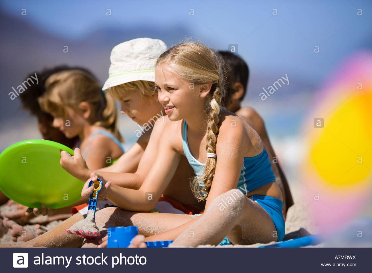 Kinder 4-9 sitzen in der Schlange am Strand Seite lächelnd ansehen differenzielle Fokus Stockbild