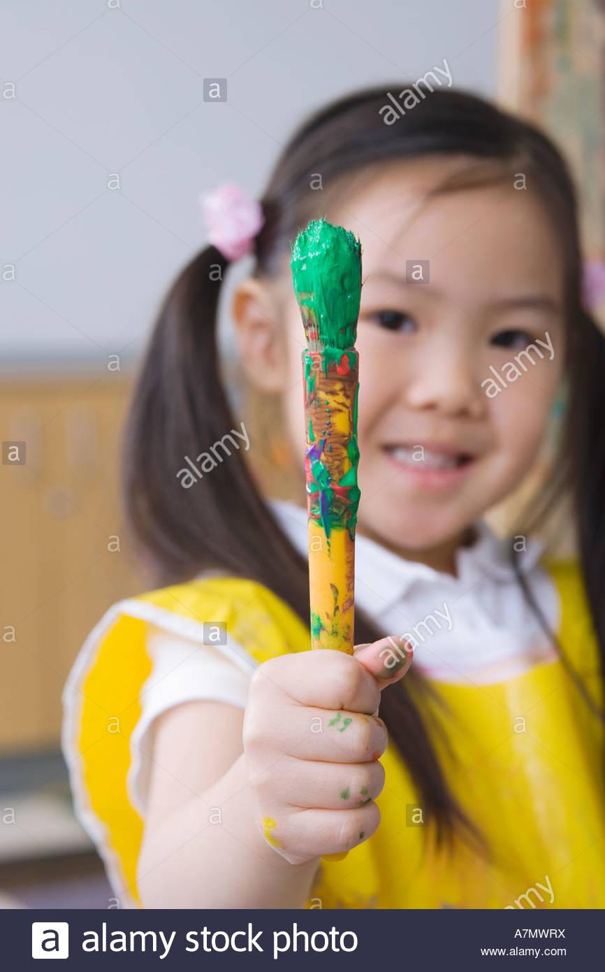 Mädchen 3 5 hält Pinsel lächelnd Vorderansicht Nahaufnahme Portrait differenzierte Fokus Stockbild