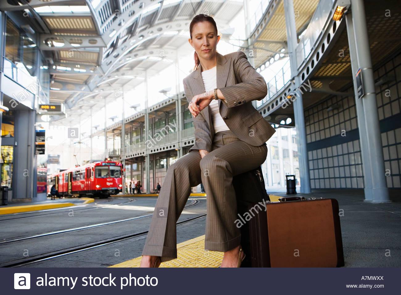 Geschäftsfrau, die sitzen auf Koffer wartet Straßenbahn Überprüfung Zeit auf Oberflächenniveau Stockbild