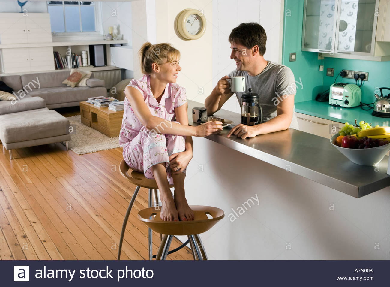 paar im pyjama sitzt auf k che fr hst ck bar frau mit f en auf hocker l chelnd seitenansicht. Black Bedroom Furniture Sets. Home Design Ideas
