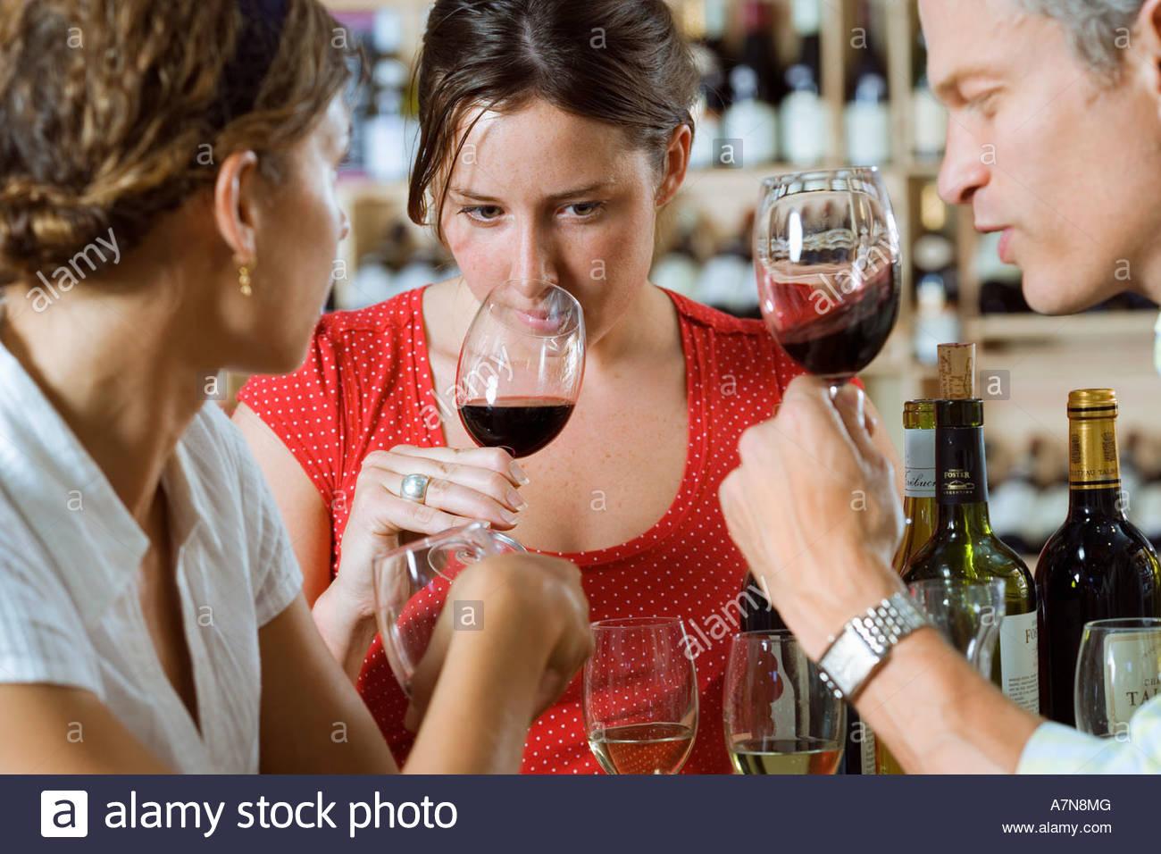 Freunde-Weinprobe in aus Lizenz Frau riechen Glas Rot Wein differenzielle Fokus Stockbild