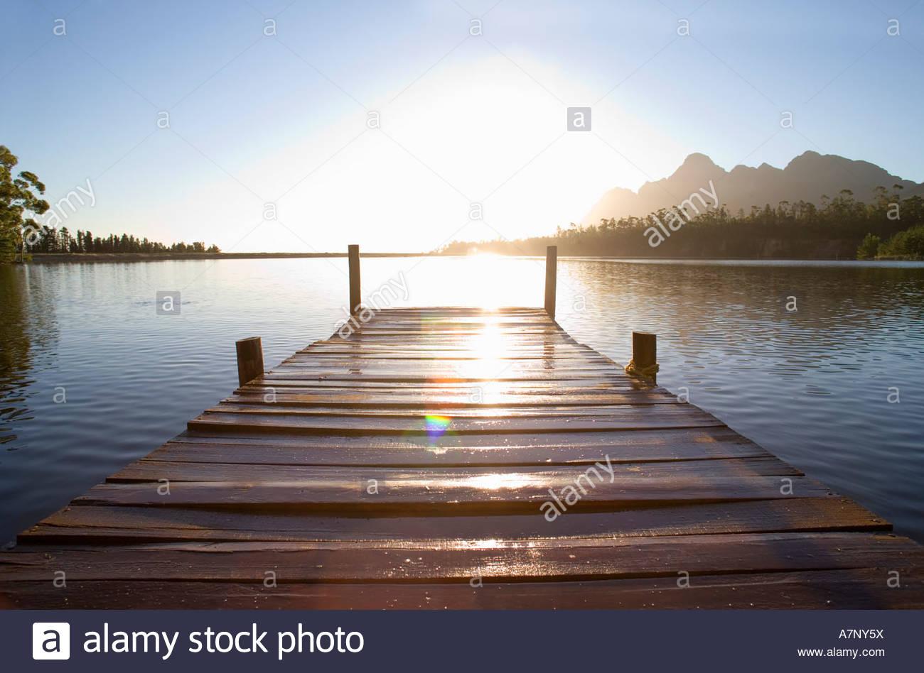 Südafrika-Holzsteg auf ruhigen See bei Sonnenuntergang Lens flare Stockbild